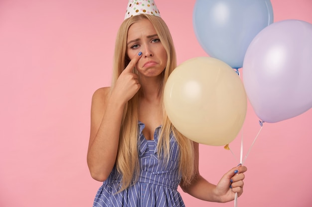 Zdenerwowana długowłosa blondynka w pozowaniu w niebieskiej letniej sukience i czapce urodzinowej w kształcie stożka, trzymająca wielobarwne balony powietrzne, patrząc na kamerę, niestety ocierając łzy, odizolowana na różowym tle