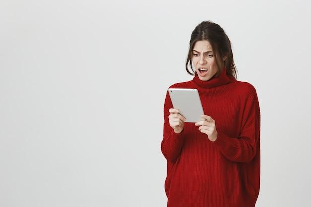 Zdenerwowana dziewczyna patrząc na cyfrowy tablet zły