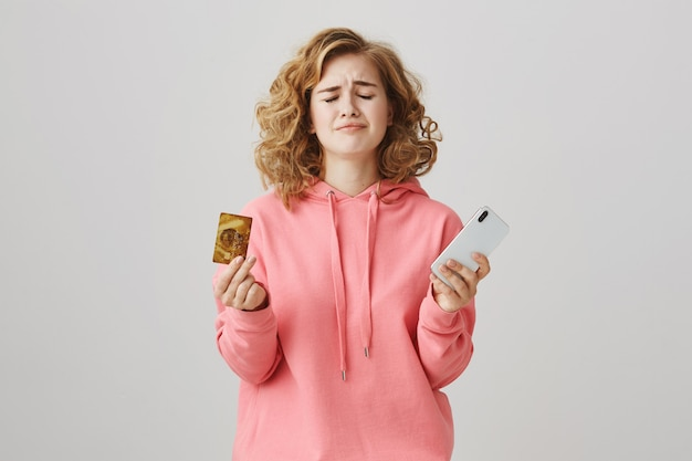 Zdenerwowana dziewczyna z kręconymi włosami marszczy brwi, nie mając pieniędzy na koncie, trzyma telefon komórkowy