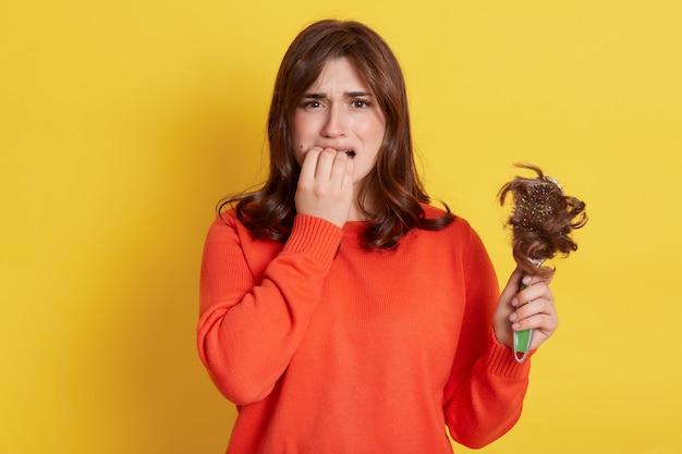 Zdenerwowana europejska kobieta ubrana w pomarańczowy sweter o wypadaniu włosów