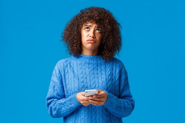 Zdenerwowana i niespokojna afroamerykańska ponura dziewczyna czuje się jak przegrana, patrząc w niebo pytając boga dlaczego, wzdychając smutno, trzymając smartfon, stojąc niespokojnie i dąsając się na niebiesko