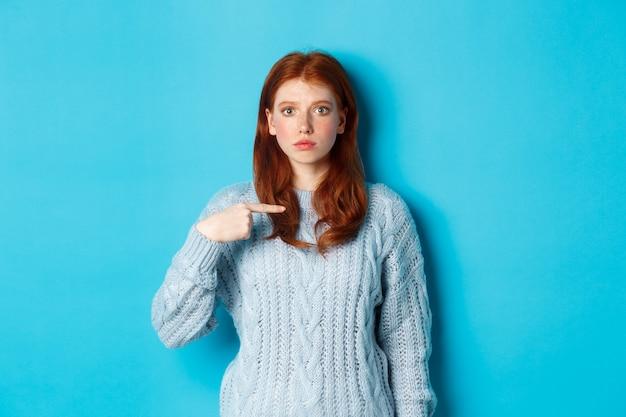 Zdenerwowana i zdezorientowana ruda dziewczyna wskazuje na siebie, stojąc w swetrze na niebieskim tle.