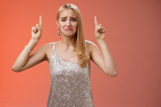 Zdenerwowana, jęcząca niedojrzała, zepsuta blond bogata dziewczyna w srebrnej błyszczącej sukni dąsająca się i marszcząca brwi będzie płakać wskazując w górę żal zazdrość błagająca o kupienie drogich butów, stojąc niezadowolona na czerwonym tle.