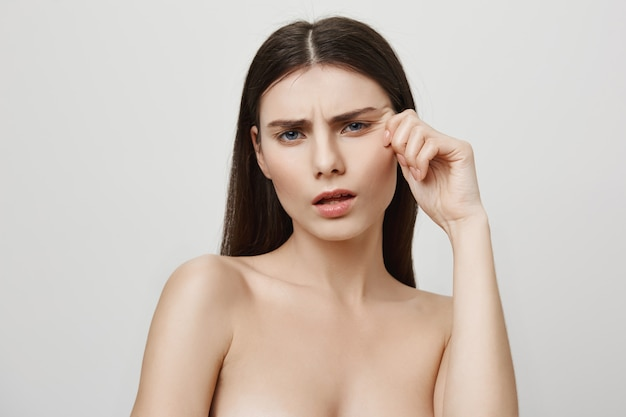 Zdenerwowana kobieta narzeka na zmarszczki twarzy, pojęcie piękna i kosmetologii