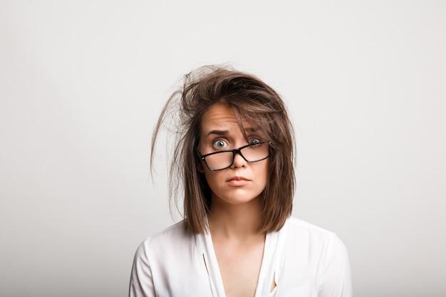 Zdenerwowana, kobieta o rozczochranych włosach i przygnębionym spojrzeniu
