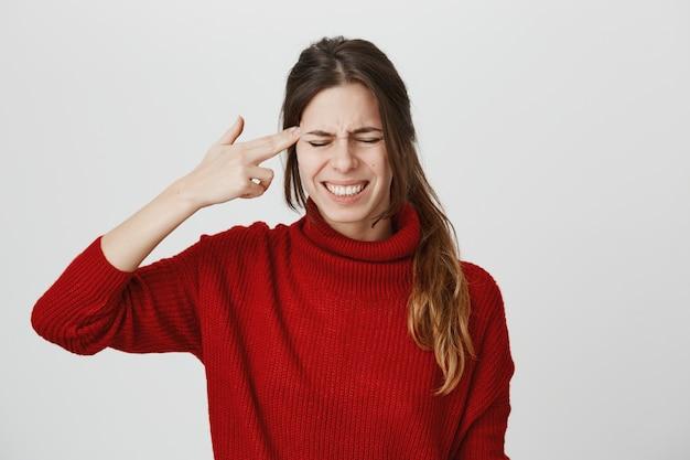Zdenerwowana kobieta robi znak pistoletu nad świątynią