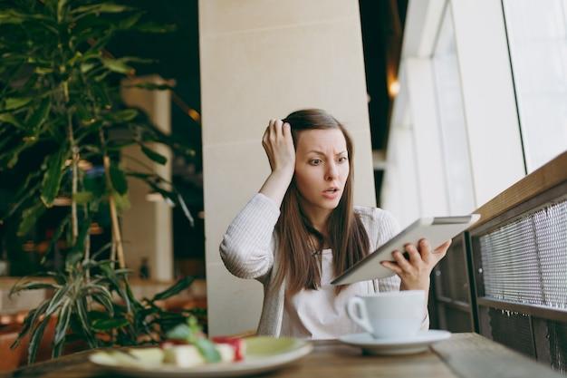 Zdenerwowana kobieta siedzi samotnie w pobliżu dużego okna w kawiarni z filiżanką cappuccino, ciasto, relaks w czasie wolnym. kobieta pracująca, czytając złe wieści na komputerze typu tablet pc odpocząć w kawiarni. koncepcja stylu życia