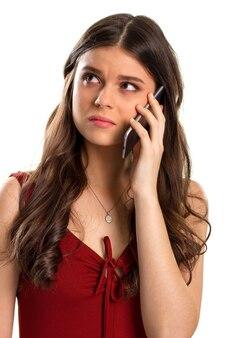 Zdenerwowana kobieta trzyma telefon komórkowy. czerwona sukienka i mała zawieszka. słyszała nieprzyjemne rzeczy. nie smuć się.