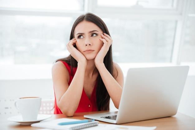 Zdenerwowana kobieta w czerwonej koszuli siedzi przy stole z laptopem i dokumentami w biurze. jak kobieta odwracająca wzrok