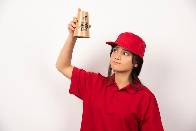 Zdenerwowana kobieta w czerwonym mundurze trzyma pusty kubek