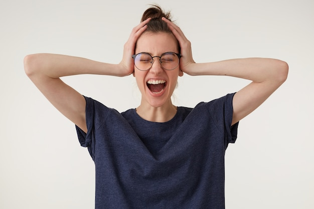 Zdenerwowana kobieta w panice krzyczy, zamykając oczy i trzymając się za głowę