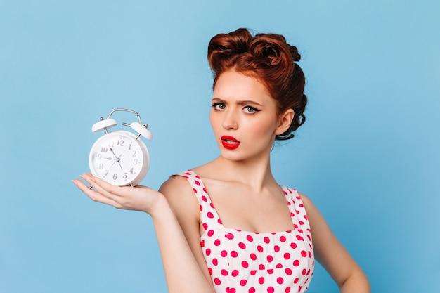 Zdenerwowana kobieta z jasnym makijażem pokazuje czas. studio strzałów pięknej dziewczyny pinup z zegarem.