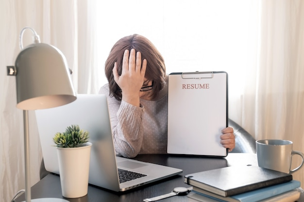 Zdenerwowana kobieta zamknęła twarz rąk w pobliżu jej pracy z laptopem i wznowić aplikację.