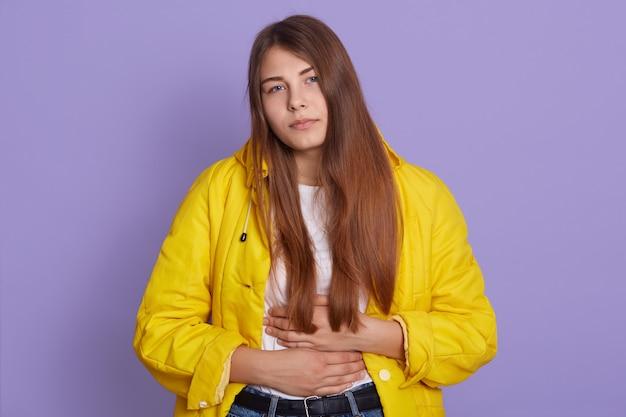 Zdenerwowana kobieta ze smutnym wyrazem twarzy, trzymająca ręce na brzuchu, cierpiąca na ból brzucha, pozująca odizolowana na fioletowej ścianie.