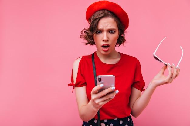Zdenerwowana krótkowłosa dziewczyna czytająca wiadomość telefoniczną. kryty zdjęcie zdziwionej francuskiej modelki w berecie z otwartymi ustami.