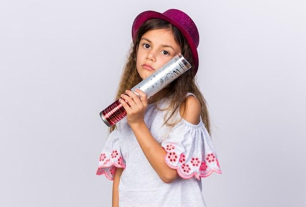 Zdenerwowana mała kaukaska dziewczynka w fioletowym kapeluszu imprezowym trzymająca armatę konfetti na białej ścianie z miejscem na kopię