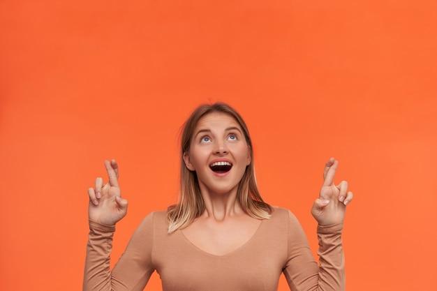 Zdenerwowana młoda atrakcyjna krótkowłosa blondynka ubrana w beżową bluzkę, unosząca ręce ze skrzyżowanymi palcami i patrząca podekscytowana w górę, stojąca nad pomarańczową ścianą