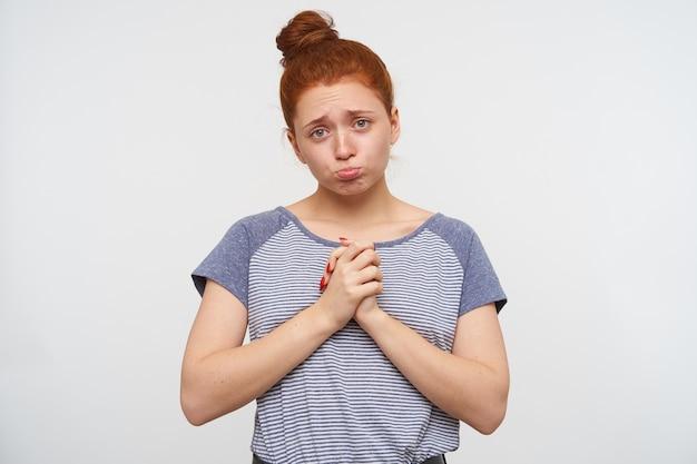 Zdenerwowana młoda atrakcyjna rudowłosa kobieta z swobodną fryzurą trzymająca uniesione ręce razem i wydrążająca usta, patrząc smutno, stojąc nad białą ścianą