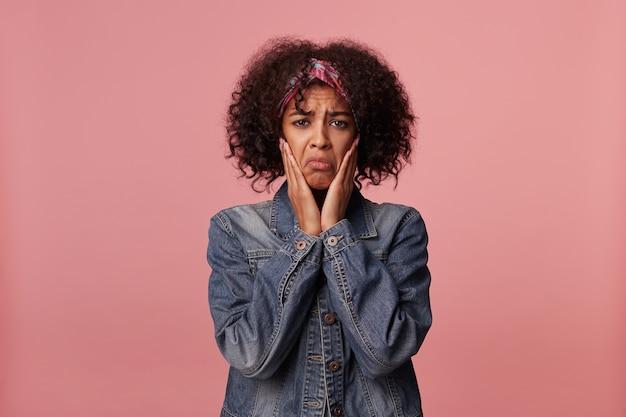 Zdenerwowana młoda ciemnoskóra brunetka kobieta z krótkimi kręconymi włosami trzymająca dłonie na policzkach i smutno wyglądająca, wykrzywiająca usta i marszczące brwi