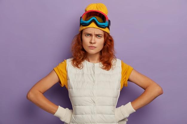 Zdenerwowana młoda europejka o rudych włosach, trzymająca ręce w pasie, marszczy czoło ze złości, nosi gogle narciarskie, wyraża negatywne emocje.