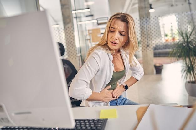 Zdenerwowana młoda kobieta odczuwa ból brzucha siedząc przy stole z komputerem w pracy