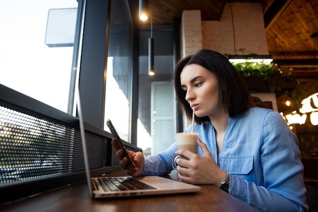 Zdenerwowana młoda kobieta patrząca na smartfona i przewijająca