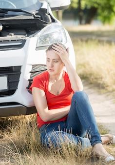 Zdenerwowana młoda kobieta siedzi na ziemi i opiera się na zepsutym samochodzie
