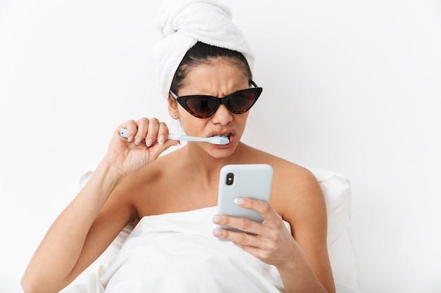 Zdenerwowana młoda kobieta siedzi w łóżku po prysznicu owinięta w koc, nosi okulary przeciwsłoneczne, używa telefonu komórkowego, myje zęby