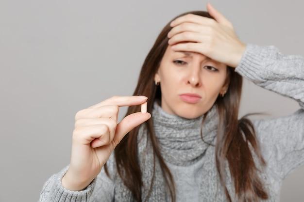Zdenerwowana młoda kobieta w szarym swetrze, szalik, kładąc rękę na czole, przytrzymaj tabletkę leków, pigułkę aspiryny na białym tle na szarym tle. zdrowy styl życia, leczenie chorych chorych, koncepcja zimnej pory roku.
