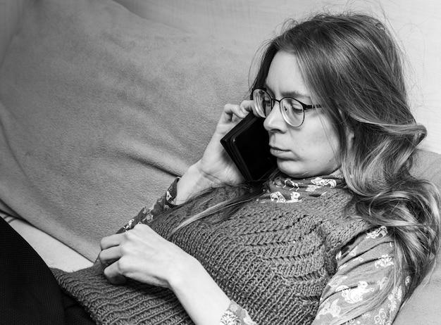 Zdenerwowana młoda kobieta z smartphone w jej ręce rozmawia przez telefon siedząc na kanapie w domu. czarno-białe zdjęcie.