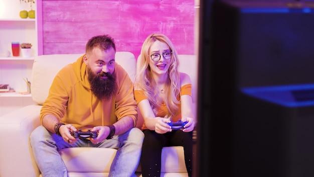 Zdenerwowana młoda para po przegranej podczas grania w gry wideo online za pomocą bezprzewodowych kontrolerów. rozczarowanie na ich twarzach