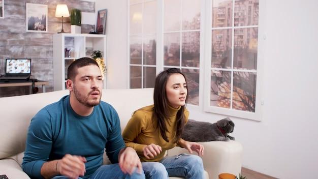 Zdenerwowana młoda para podczas oglądania meczu w telewizji. kot siedzi na kanapie. pizza, napoje gazowane i popcorn na stoliku do kawy.