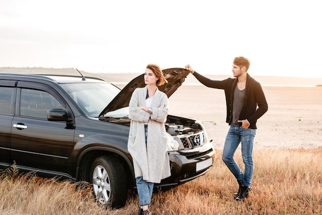 Zdenerwowana młoda para stojąca w pobliżu samochodu z otwartym kapturem na zewnątrz