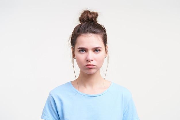 Zdenerwowana młoda piękna brunetka kobieta ubrana w brązowe włosy w węzeł, pozując na białej ścianie, trzymając usta złożone, patrząc smutno z przodu