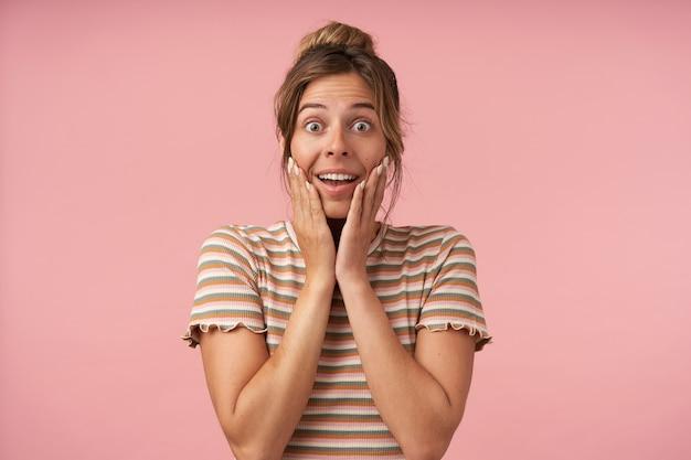 Zdenerwowana młoda śliczna brązowowłosa dama trzymająca dłonie na policzkach, patrząc podekscytowana na aparat z szeroko otwartymi oczami, odizolowana na różowym tle