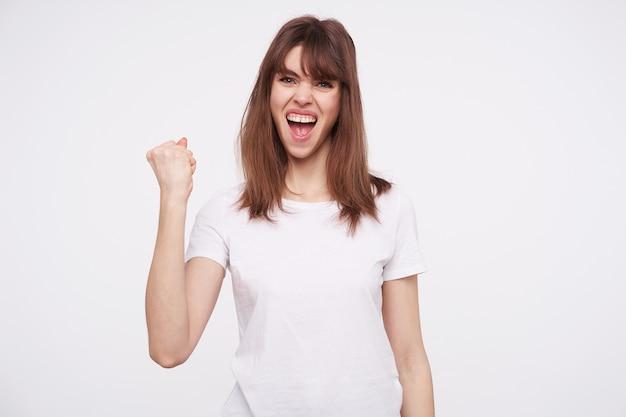 Zdenerwowana młoda śliczna brązowowłosa dama z przypadkową fryzurą krzycząca radośnie z szeroko otwartymi ustami i pokazująca pięść podczas pozowania na białej ścianie