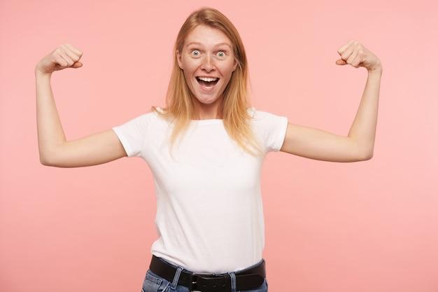 Zdenerwowana młoda, urocza ruda kobieta z naturalnym makijażem podnosząca ręce, demonstrując swoją moc, z podekscytowaniem patrząc na kamerę, pozując na różowym tle