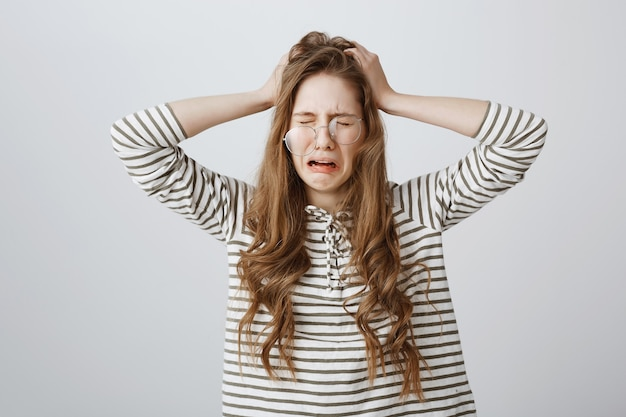 Zdenerwowana nieszczęśliwa dziewczyna płacze i trzyma ręce na głowie zdenerwowana