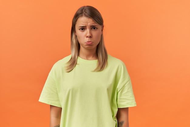 Zdenerwowana, obrażona młoda kobieta w żółtej koszulce wygląda na rozczarowaną, a wargi torebki izolowane nad pomarańczową ścianą patrząc na przód
