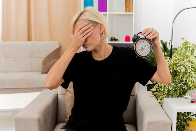 Zdenerwowana piękna blondynka rosjanka siedzi na fotelu, zamykając twarz ręką i trzymając budzik w salonie