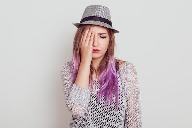 Zdenerwowana piękna kobieta z liliowymi włosami w koszuli i kapeluszu jest smutna, zasłaniająca połowę twarzy dłonią, trzyma zamknięte oczy, odizolowana na białej ścianie.