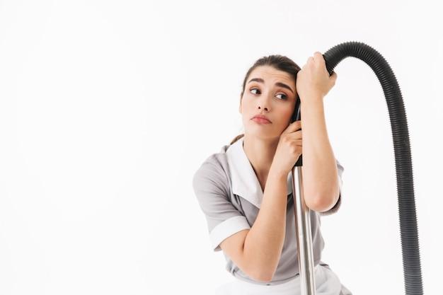 Zdenerwowana pokojówka w wieku 20 lat ubrana w jednolite sprzątanie podłogi z odkurzaczem podczas prac domowych na białym tle nad białą ścianą
