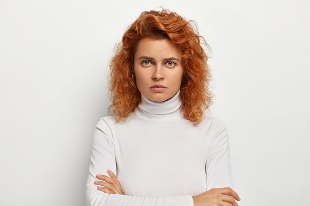 Zdenerwowana ponura ruda kobieta stoi z założonymi rękami, dąsa się i marszczy brwi, jest na kogoś zła, patrzy nienawistnie na aparat