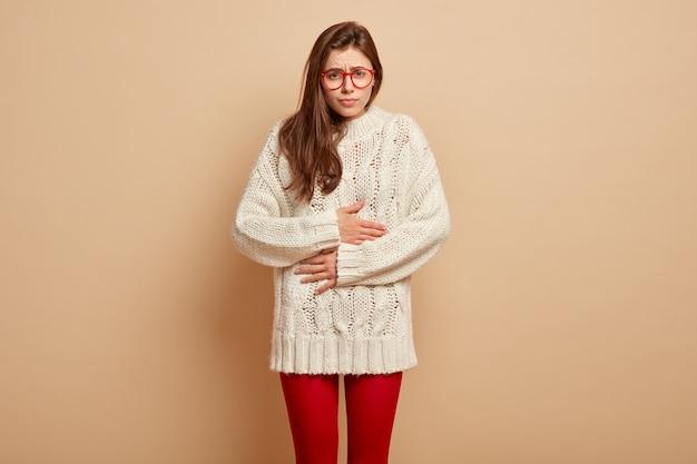 Zdenerwowana posępna europejka dotyka z bólu brzucha, źle się czuje, dyskomfort po zjedzeniu zepsutego produktu, nosi okulary i ciepłe ubranie, stoi nad brązową ścianą. koncepcja bólu brzucha
