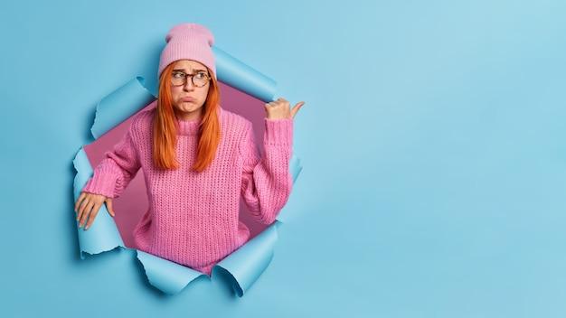 Zdenerwowana, przygnębiona kobieta z rudymi włosami jest w przygnębieniu, wskazując na przestrzeń kopii z niezadowolonym wyrazem twarzy