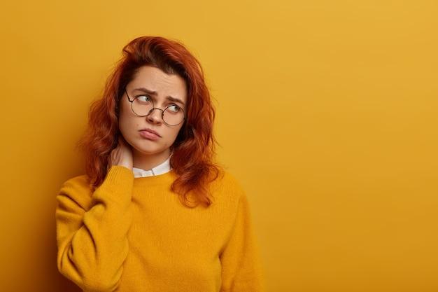 Zdenerwowana ruda kobieta odchyla głowę, cierpi na ból szyi, patrzy na bok z niezadowoleniem, nosi żółty sweter, różowe okulary, prowadzi siedzący tryb życia, potrzebuje masażu