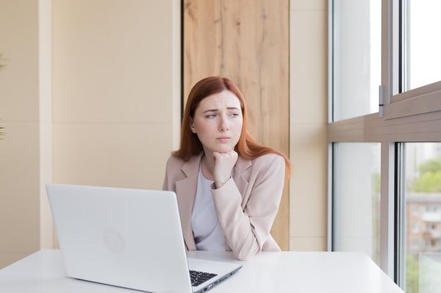 Zdenerwowana rudowłosa biznesowa kobieta pracująca przy komputerze siedząca w biurze