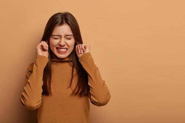 Zdenerwowana sfrustrowana kobieta zatyka uszy, zaciska zęby, słyszy dokuczliwy hałas, unika nieprzyjemnych dźwięków, nosi brązowe ubrania, nie słyszy
