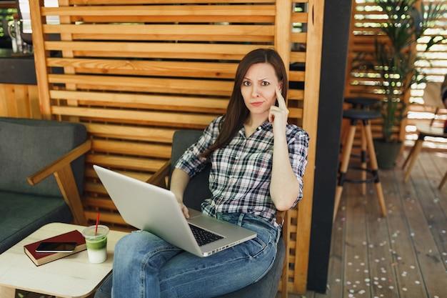 Zdenerwowana smutna dziewczyna na zewnątrz ulicy letnia kawiarnia drewniana kawiarnia siedząca w zwykłych ubraniach, pracująca na nowoczesnym komputerze typu laptop pc, w czasie wolnym