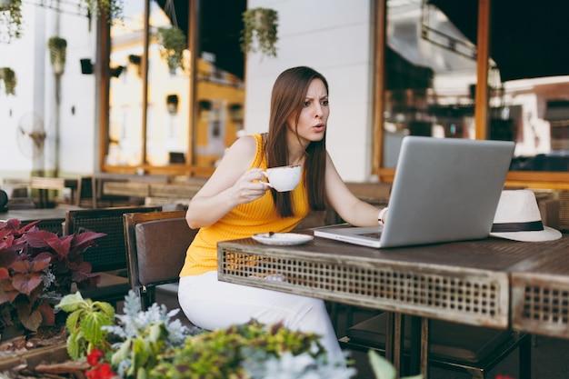 Zdenerwowana smutna kobieta w kawiarni na zewnątrz ulicy kawiarnia siedzi przy stole, pracując na nowoczesnym komputerze typu laptop, zakłócać problem w restauracji w czasie wolnym